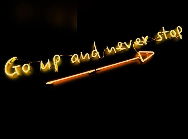 Schwarzer Hintergrund mit Schriftzug aus Leuchtstoffröhren Go up and never stop