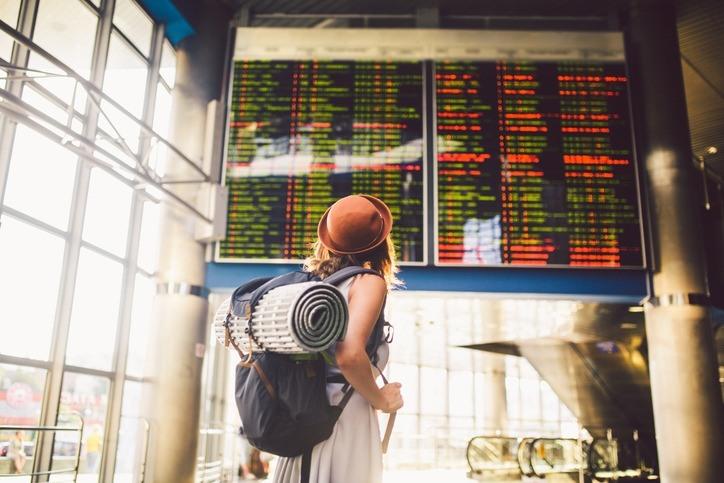 Eine Frau steht vor einer Anzeigetafel am Flughafen.