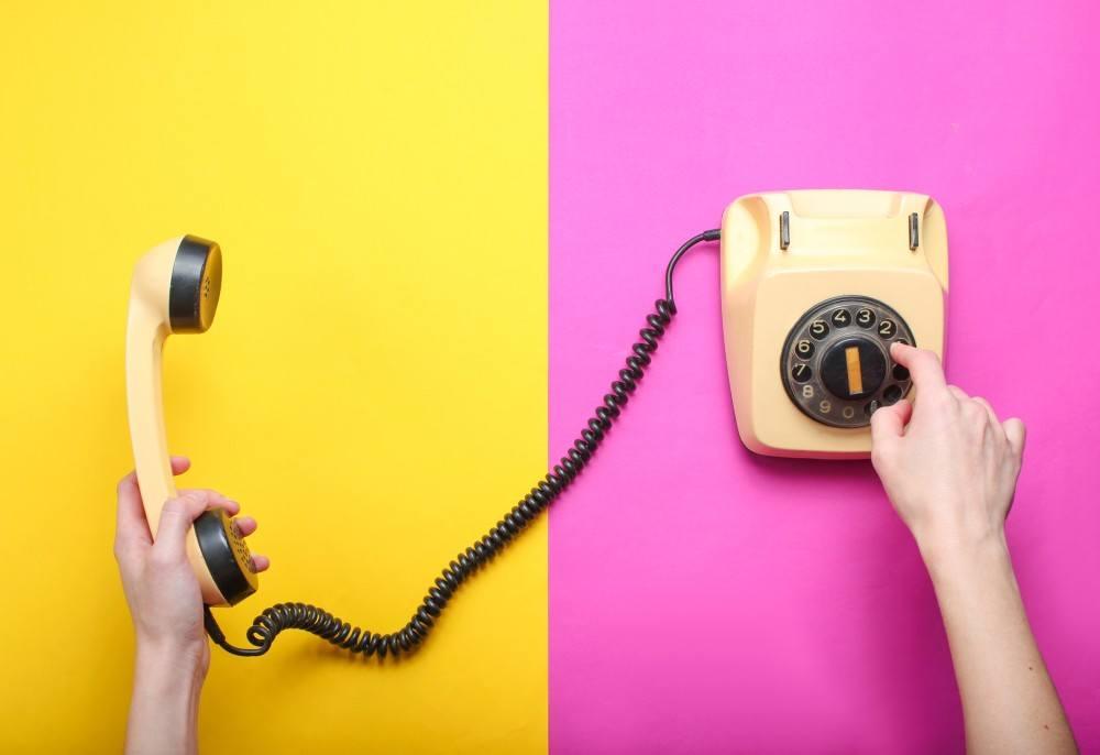 altes Schnurtelefon mit Wählscheibe auf farbigen Untergrund
