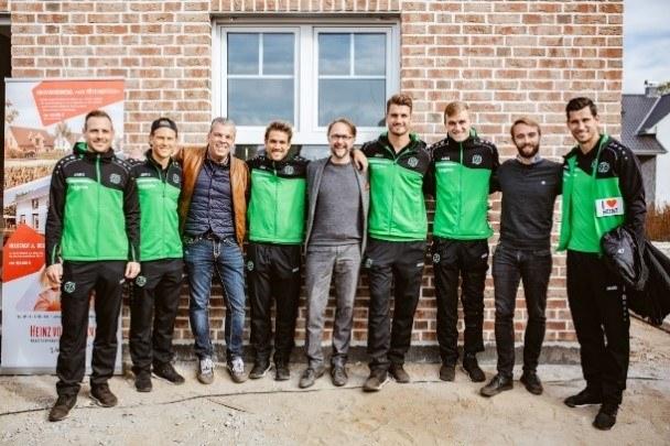 Dr. Helge Mensching im Kreis mit Fußballprofis von Hannover 96