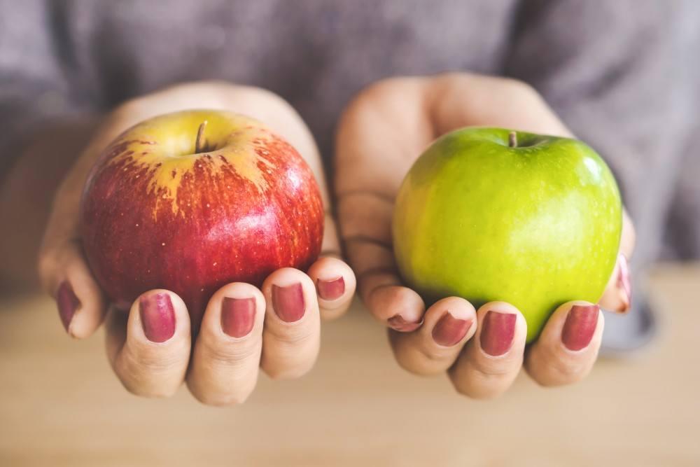 roter und grüner Apfel jeweils in einer Hand
