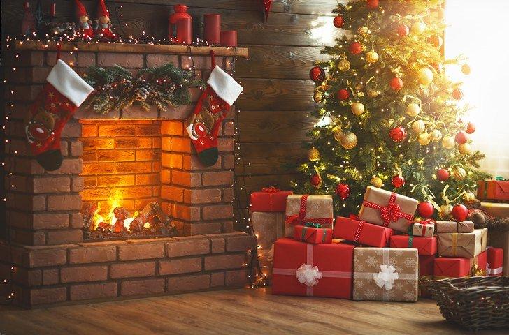 Ein weihnachtlich geschmücktes Wohnzimmer mit Weihnachtsbaum, Geschenken und Kamin