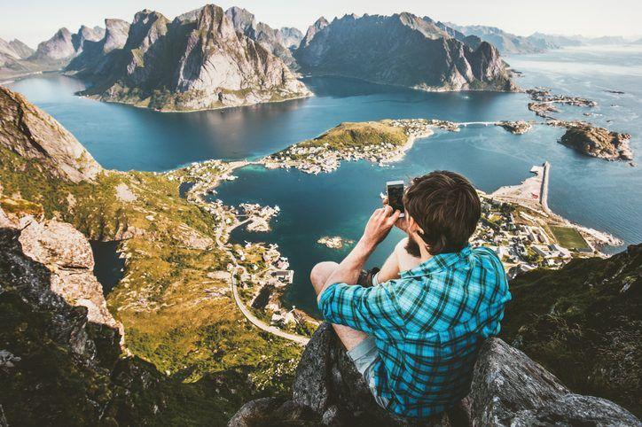 Ein Mann mit Handy auf einem Berg