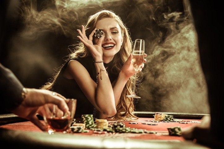 Frau mit Getränk und Poker-Chip