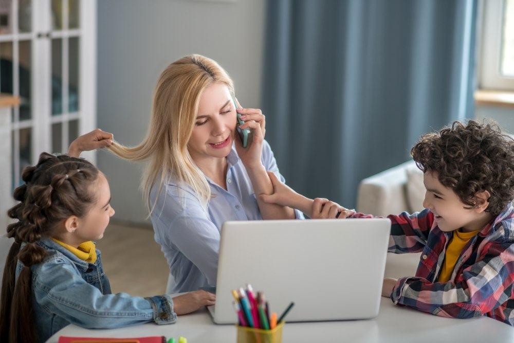 Frau sitzt vor Notebook mit zwei Kindern