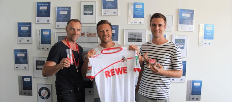 Friedhelm Mienert, Felix Benckendorff und Lukas Schuhmacher halten Produkte vom FC Köln