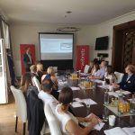 Mehrere Personen verfolgen eine Präsentation an einem Konferenztisch