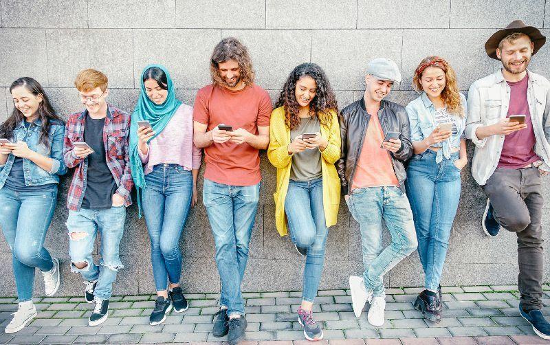 acht junge Menschen stehen gelehnt vor einer Mauer und schauen auf ihr Handy