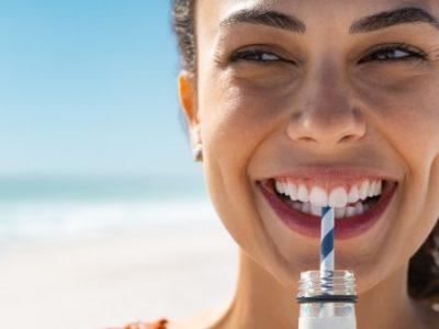Eine Frau trinkt ein Getränk am Strand