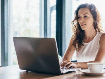 Frau sitzt zuhause und benutzt ihren Laptop