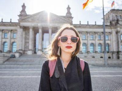 Frau steht vor dem Reichstagsgebäude in Berlin