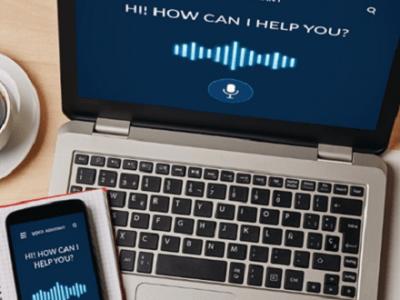 Blick auf Laptop mit Smartphone und Sprachassisten