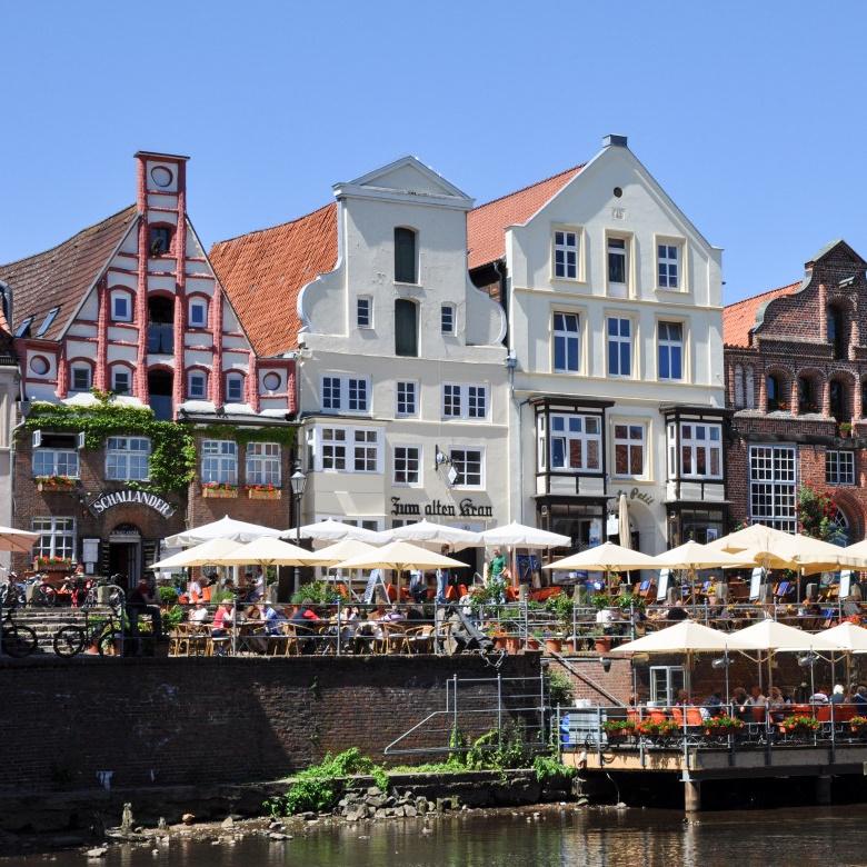 Aufnahme des Stint in Lüneburg, mit der Ilmenau im Vordergrund sowie Restaurants im Hintergrund