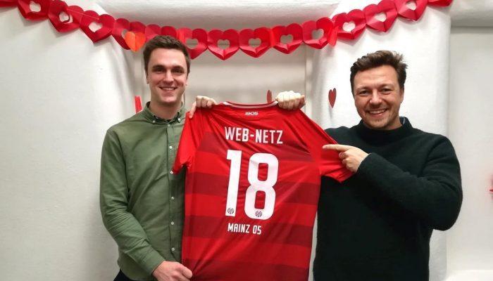 Lukas Schumacher und Felix Benckendorff halten ein Trikot von Mainz 05 in die Kamera
