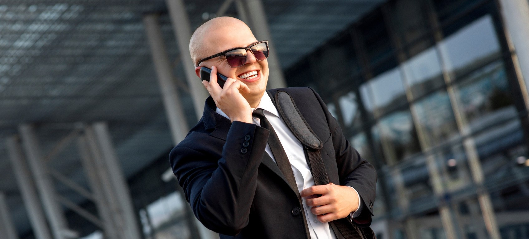 Businessman or banker speaking phone outside the airport or contemporary building