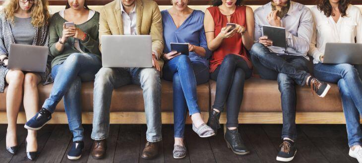 Menschen mit digitalen Geräten auf Sofa