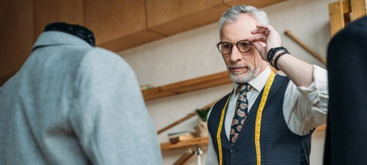 handsome tailor touching glasses and looking at jackets on mannequins at sewing workshop