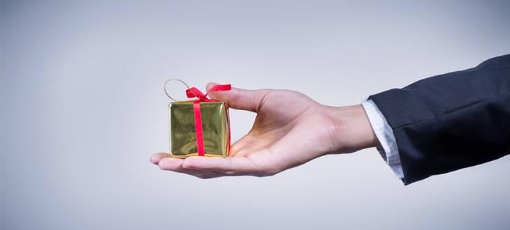 Ausgetreckte hand reicht kleines Geschenk