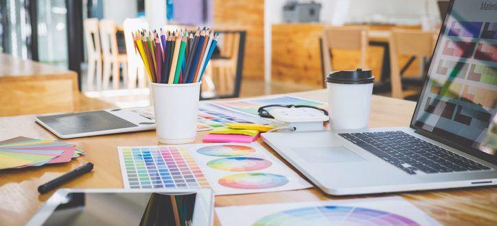 Schreibtisch voller Arbeitsmaterialien eines Mediengestalters