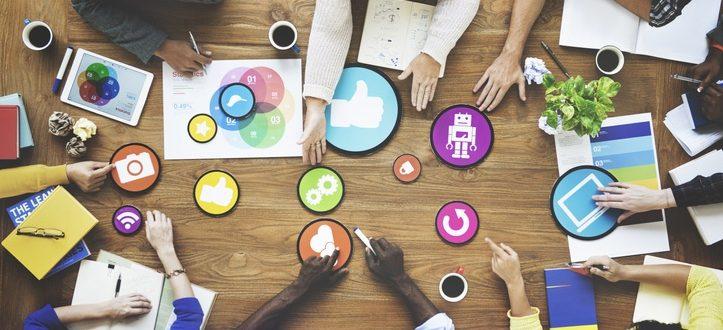 Verschiedene Online Marketing Symbole auf einem Tisch - mehrere Personen tauschen sich dazu aus