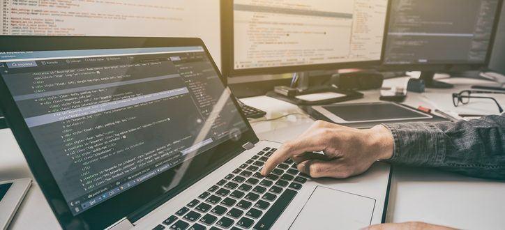 Person sitzt vor einem Schreibtisch mit einem Laptop und mehreren PC-Bildschirmen im Hintergrund