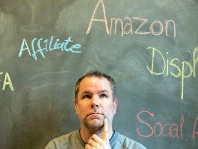 Mann sitzt vor Tafel mit den Aufschriften SEA Affiliate Amazon Display und Social Ads