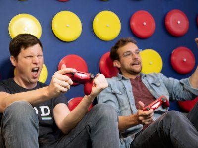 Mitarbeiten im Spielzimmer der Agentur web-netz mit vollem EInsatz spielend an der Playstation.