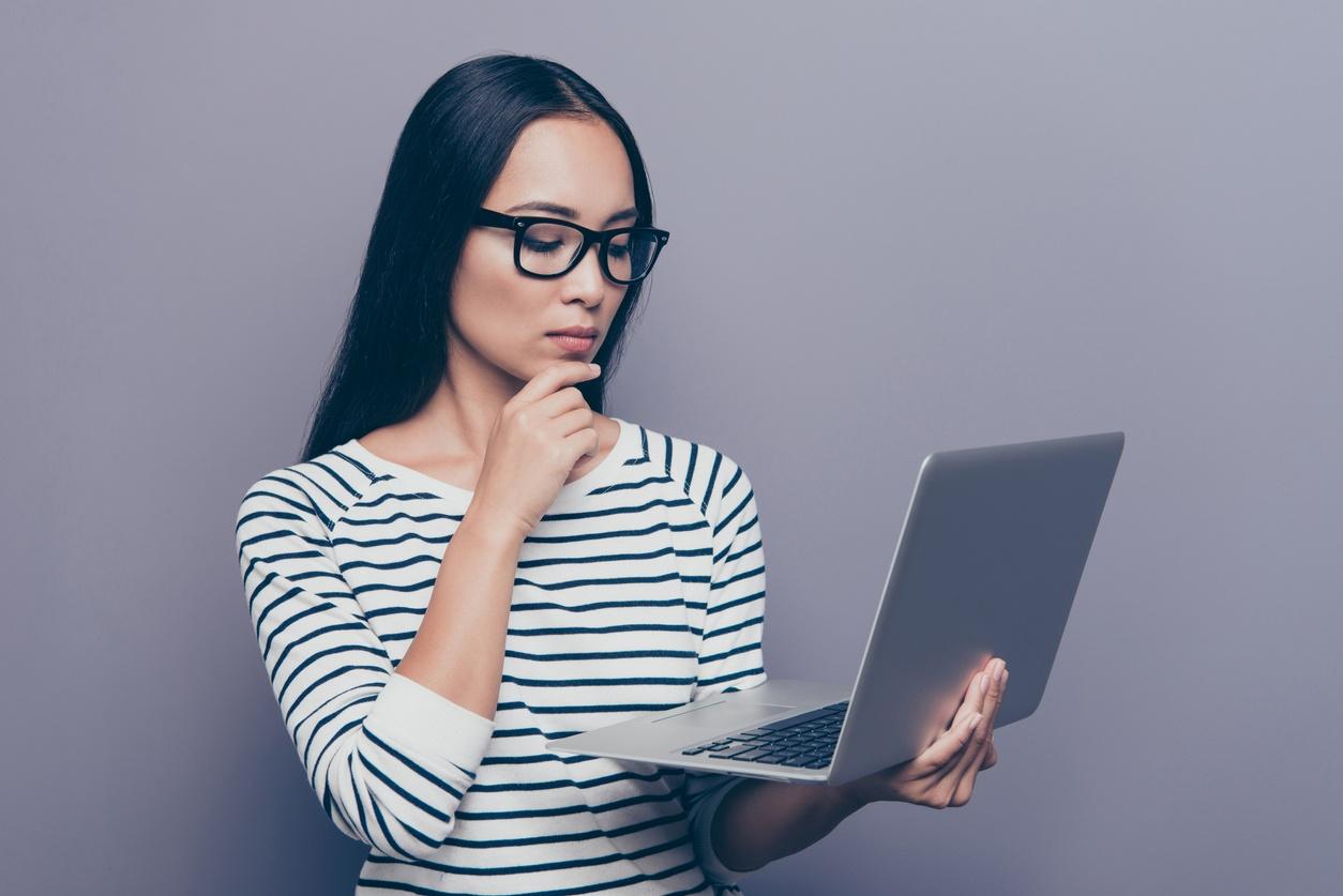 Eine Frau schaut fokussiert auf ihren Laptop