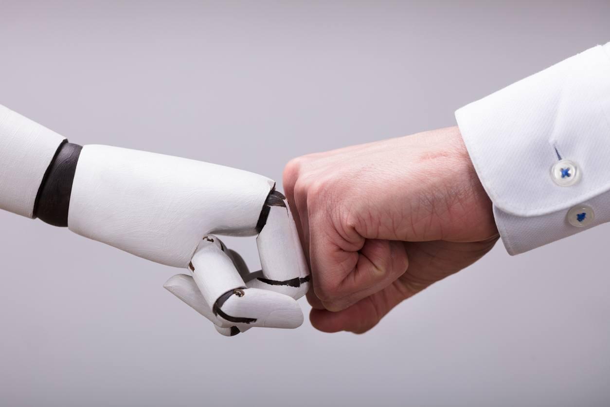 Roboterfaust berührt Faust eines Mannes